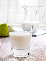 Close_up of a glass of milk with a pitcher in the background