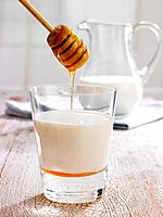 Close_up of honey being poured into a glass of milk