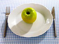 Close_up of an apple in a plate with a table knife and a fork