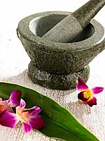 Close_up of flowers and a leaf with a mortar and a pestle