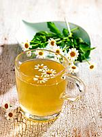 Close_up of a cup of chamomile tea with flowers