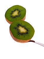 Close_up of two halves of a kiwi fruit with a spoon