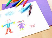 Close_up of a child's drawing on a sheet of paper with colored pencil