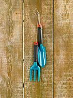 Trowel and gardening fork hanging on a wooden plank