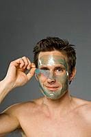Close_up of mid adult man peeling facial mask