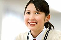 Teenage girl smiling and looking up, front view