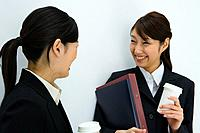 Two young businesswomen smiling and talking, holding paper cups, front view, side view, white background, Japan