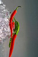 Green and Red Hot Chili Peppers pushed through water