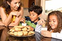 Portrait of mom and kids eating cookies