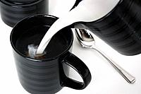 Pouring cream into black coffee mug