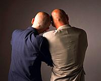 Two bald headed businessmen leaning on each other, Rear View