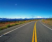 an Asphalt Road Under a Deep Blue Sky and Some Snowy Mountains in the Background