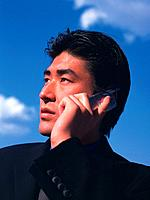 Businessman using a mobile phone under the blue sky, low angle view