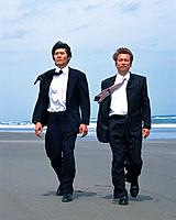 Image of Two Businessmen Walking at the Beach, the Wind Blowing Through Their Hair, Front View