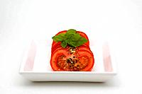 Tomato slices with oregano on plate and white background