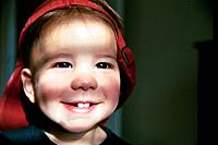 Boy Wearing An Oversized Red Hat And Smiling