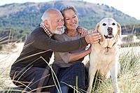 Senior couple stroking a dog