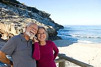 Senior couple using cell phone at beach