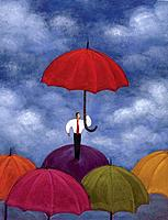 Businessman standing under red umbrella while standing atop several umbrellas