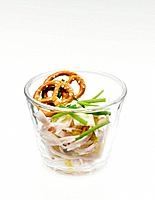 Sausage salad with salted pretzel in glass