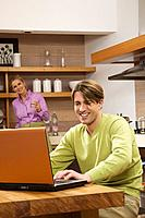 Couple in kitchen, man using laptop, smiling, portrait