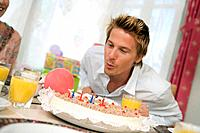 Man blowing candle on torte, portrait