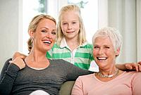 Girl 8_9 with mother and grandmother in living room, smiling, portrait