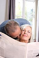 Senior man kissing senior woman, portrait