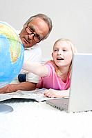 Grandfather and granddaughter 8_9 looking at globe,
