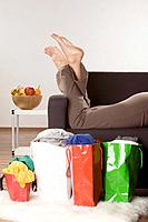 Woman relaxing on sofa, shopping bags in foreground