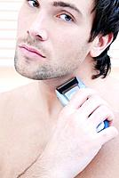 Young man using electric razor, portrait
