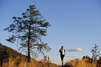 A young woman trail running on the hill tops in Penticton, British Columbia, Canada.