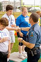 Policeman congratulating athlete at award ceremony, Special Olympics, U of M Bierman Athletic Complex, Minneapolis, Minnesota, USA