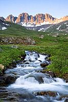 Alpenglow on peaks above American Basin with an unnamed creek rushing through green meadows, San Juan Mountains, Colorado, USA