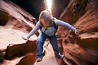 Female hiker climbs up a chokestone lodged in a narrow section of Little Wildhorse Slot Canyon in the San Rafael Swell, Utah, USA