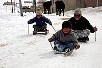 Children playing on mini sleds in winter snow near Padum, Kingdom of Zanskar, northwest India Himalaya
