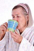 older woman, 65 + , in bathrobe drinking a cup of tea
