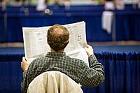 USA, Illinois: man reading newspaper while sitting in chair viewed from behind, bald spot