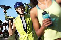 Young man carrying bicycle outdoors portrait