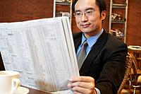 China Businessman reading newspaper at cafe table close_up