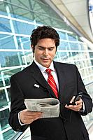 Businessman using mobile phone reading newspaper outside office building
