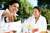 Chinese couple wearing bathrobes drinking champagne at outdoor table