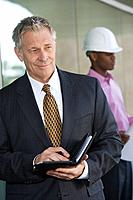 Businessman holding day planner with construction worker behind