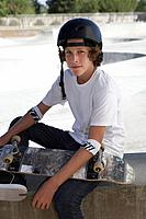 Teenage boy 16_17 with skateboard at skateboard park portrait
