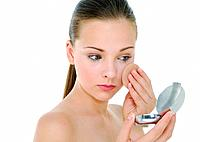 Close_up of a young woman applying face powder