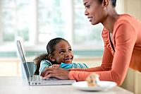 Girl Looking at Mother Using Laptop