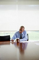 Businessman Writing at a Conference Table
