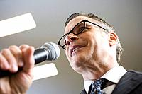 Businessman Talking into Microphone