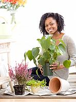 African woman holding potted plant