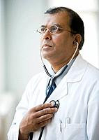 Indian male doctor holding stethoscope against chest